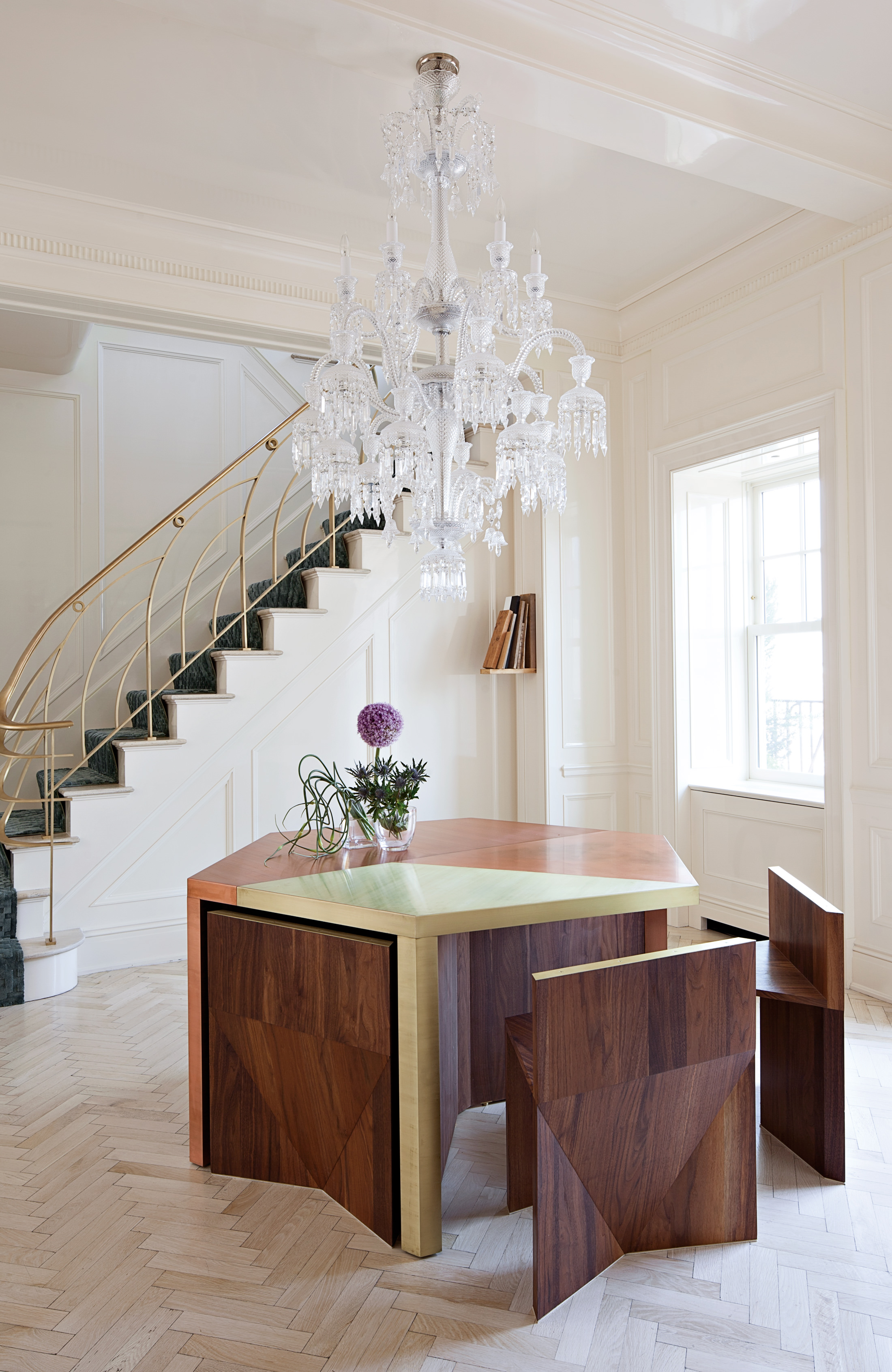 Copper and walnut hexagonal table beneath a baccarat chandelier photo floto warner and rafael de cárdenas ltd architecture at large
